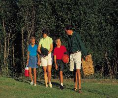 Family walking in grass with picnic items