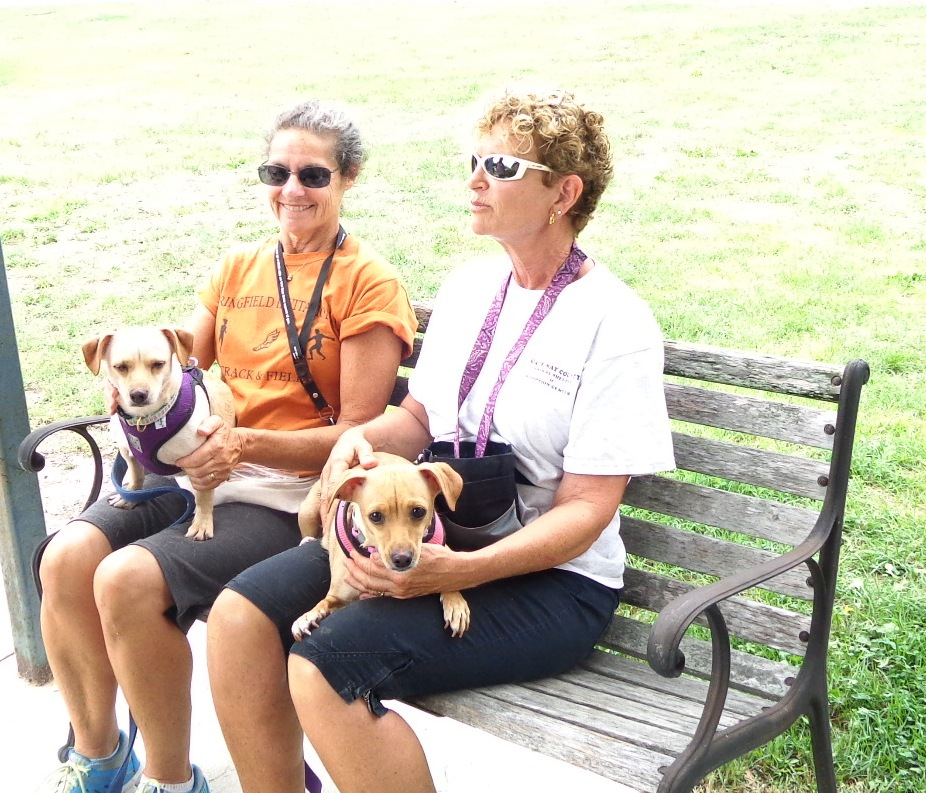 Joyce and Connie sitting on wooden bench with dogs Diva and Daisey